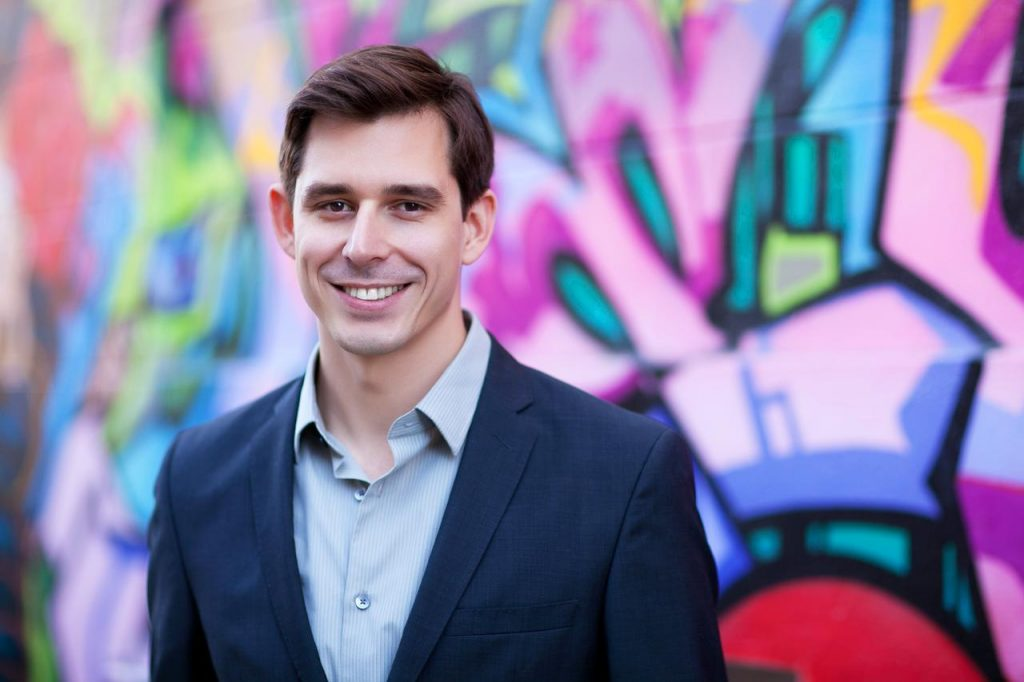 A smiling portrait of Kris Gale with a colourful graffiti backdrop.