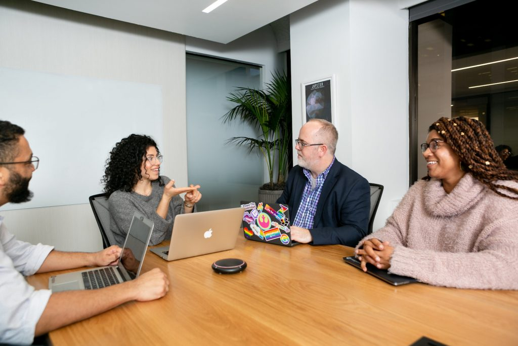 A diverse group of four coworkers chatting in a meeting room.