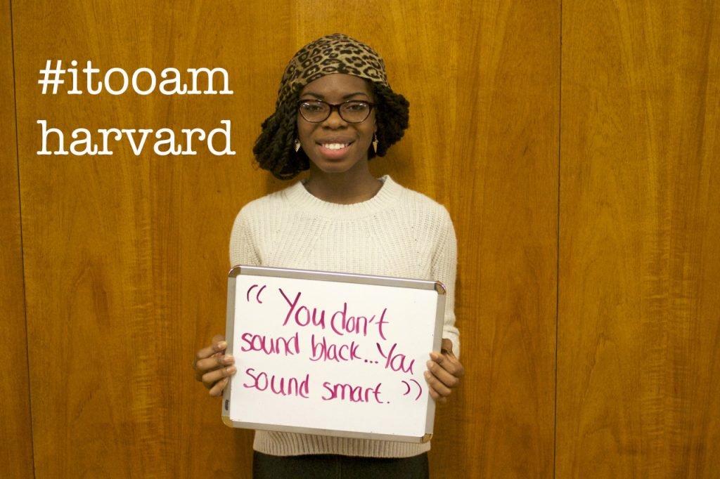 """Image of a woman holding a sign displaying a microaggression said to her """"You don't sound black, you sound smart"""""""